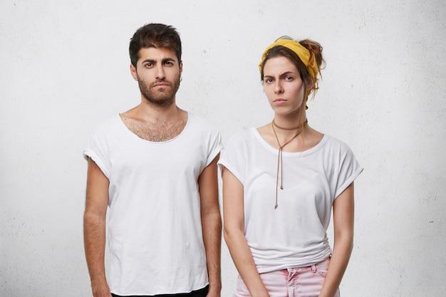 Poziomy portret zdenerwowany para w białych koszulkach dorywczo mających kłopoty w rodzinie na białym tle