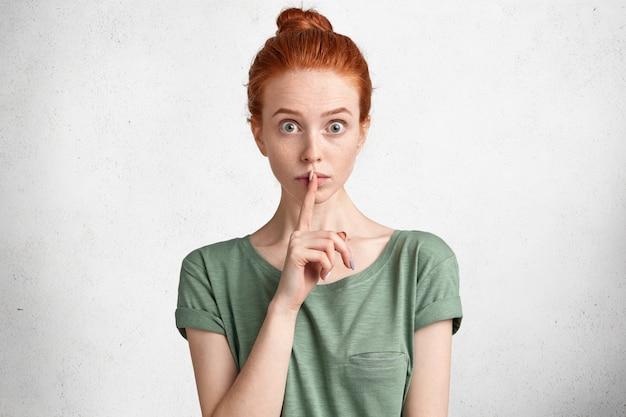 Poziomy portret zszokowanej piegowatej kobiety z węzłem rudych włosów, pokazuje znak ciszy, prosi o zachowanie poufności lub prywatności informacji, pozuje przeciwko białym