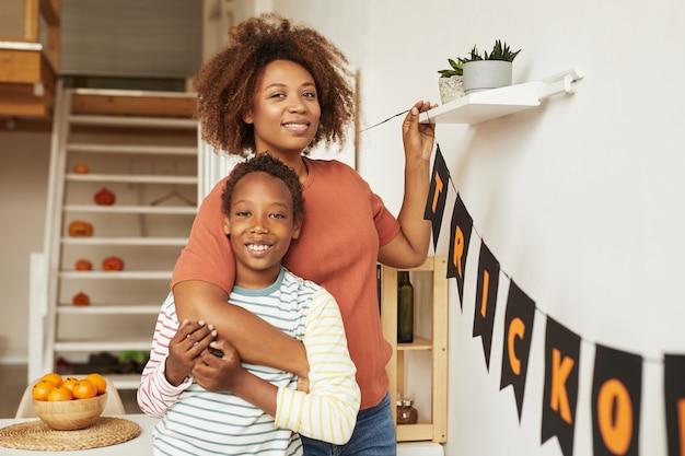 Poziomy średni portret szczęśliwej młodej dorosłej kobiety i jej wesołego syna uśmiecha się do kamery podczas dekorowania pokoju na halloween
