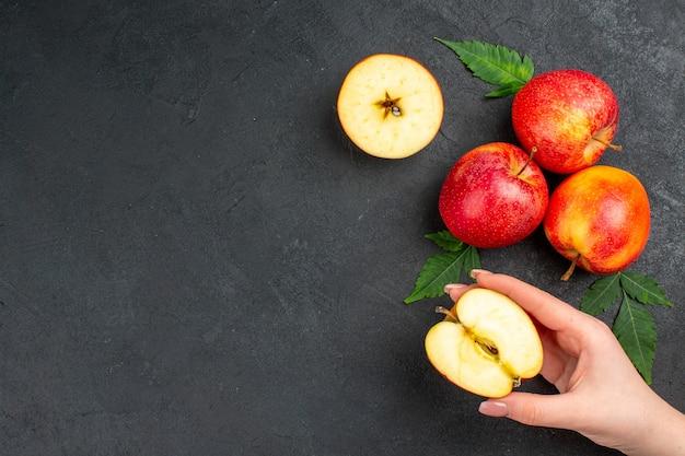 Poziomy widok całych i pokrojonych świeżych czerwonych jabłek i liści na czarnym tle