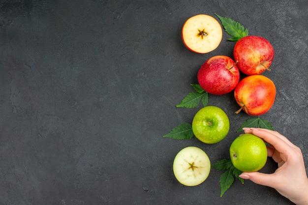 Poziomy widok całych i pokrojonych świeżych naturalnych jabłek i liści na czarnym stole