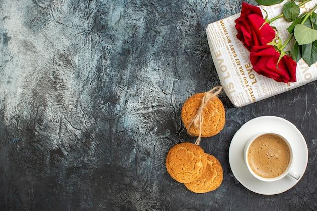 Poziomy widok czerwonej róży na pudełku prezentowym i ciasteczkach filiżanka kawy po lewej stronie na lodowatym ciemnym tle