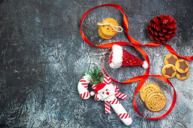Poziomy widok kapelusza świętego mikołaja i ciasteczek prezentowych z rogacza czekoladowego z czerwonym stożkiem iglastym na ciemnej powierzchni