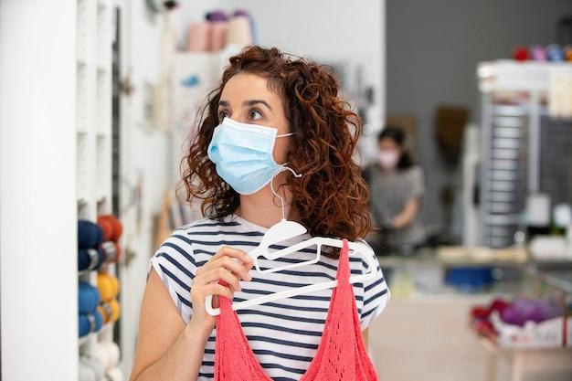 Poziomy widok kobiety noszącej maskę robiąc zakupy ubrania