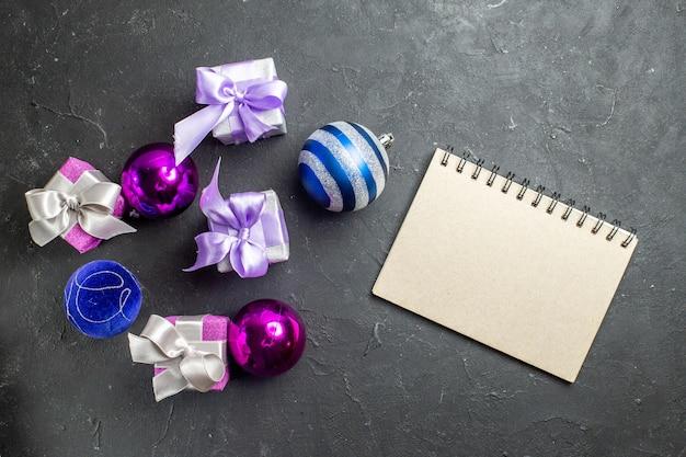Poziomy widok kolorowych prezentów i akcesoriów dekoracyjnych oraz notebooka na czarnym tle