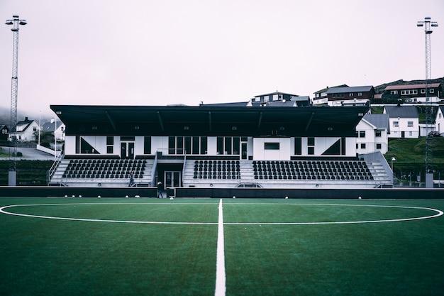 Poziomy widok małego stadionu piłkarskiego na wyspach owczych.