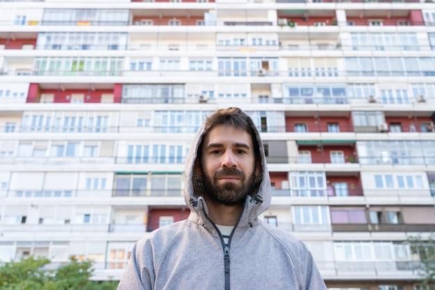 Poziomy widok młodego człowieka na białym tle przed małe tanie apartamenty na zewnątrz.