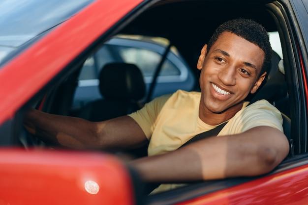 Poziomy widok młodego wielorasowego człowieka uśmiechniętego siedząc w samochodzie w miejscu kierowcy i jazdy samochodem w korku. koncepcja podróży drogowej