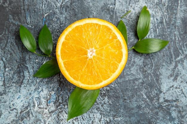Poziomy widok przekrojonej na pół świeżej pomarańczy z liśćmi na szarym tle pień fotografia