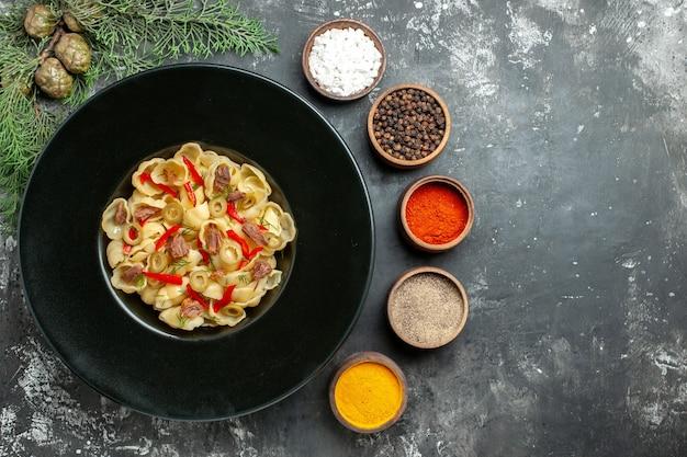Poziomy widok pysznego conchiglie z warzywami i zielenią na talerzu i nożem oraz różnymi przyprawami na szarym tle