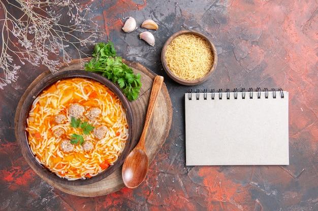 Poziomy widok pysznej zupy z makaronem z kurczakiem na drewnianej desce do krojenia zieloną łyżką czosnku i notatnikiem na ciemnym tle