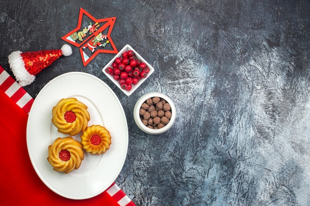 Poziomy widok pysznych herbatników na białym talerzu na czerwonym ręczniku i czapce świętego mikołaja dereń i czekoladki w białych doniczkach na ciemnej powierzchni