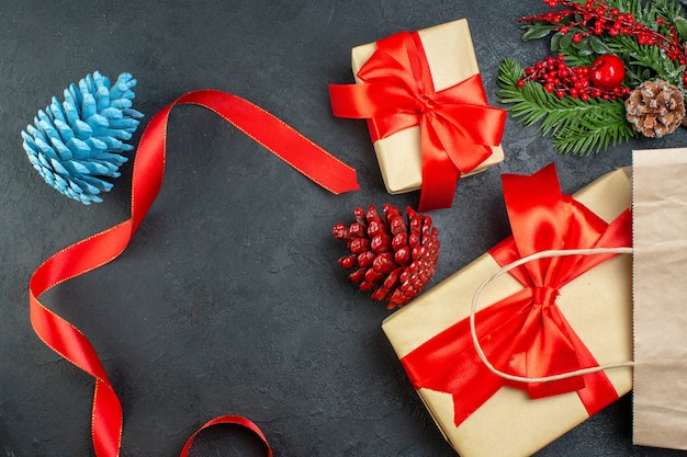 Poziomy widok rolki szyszek iglastych czerwoną wstążką i gałęzi jodły prezent na ciemnym stole