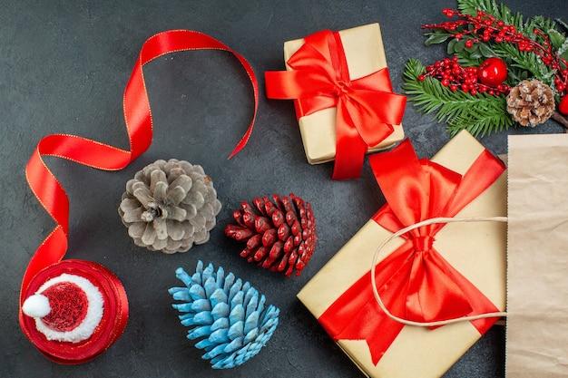 Poziomy widok rolki szyszek iglastych czerwoną wstążką i gałęzi jodły prezent na ciemnym tle