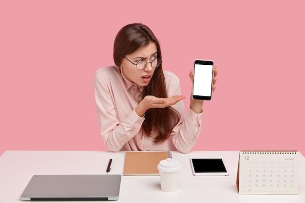 Poziomy widok sfrustrowanej kobiety pokazuje coś na pustym ekranie telefonu komórkowego