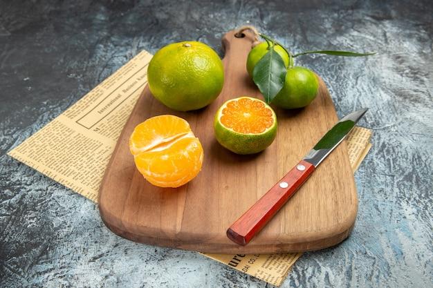 Poziomy widok świeżych owoców cytrusowych z liśćmi na drewnianej desce do krojenia pokrojonej w pół formy na gazecie na szarym tle