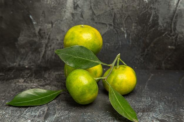 Poziomy widok świeżych zielonych mandarynek z liśćmi na szarym tle materiału
