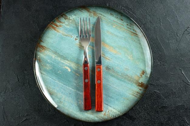 Poziomy widok sztućców do posiłków na niebieskim talerzu na ciemnej powierzchni