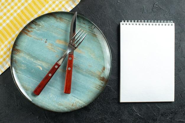 Poziomy widok sztućców do posiłków w krzyżu na niebieskim talerzu i żółtym ręczniku w paski obok notatnika na ciemnej powierzchni