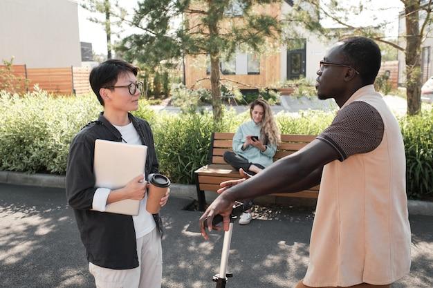 Poziomy widok z boku średni portret młodego afroamerykańskiego mężczyzny i azjatyckiej kobiety spotykających się na zewnątrz witających się i rozmawiających o czymś