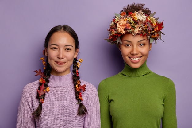 Poziomy widok zadowolonych kobiet stojących obok siebie, wyrażających pozytywne emocje, ozdabiających włosy atrybutami jesieni, odizolowanych na fioletowym tle