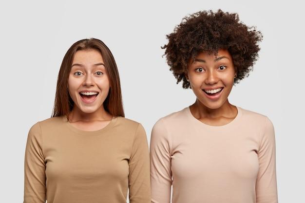 Poziomy widok zadowolonych przyjaciół rasy mieszanej, uśmiechających się radośnie, ubranych w swobodne swetry