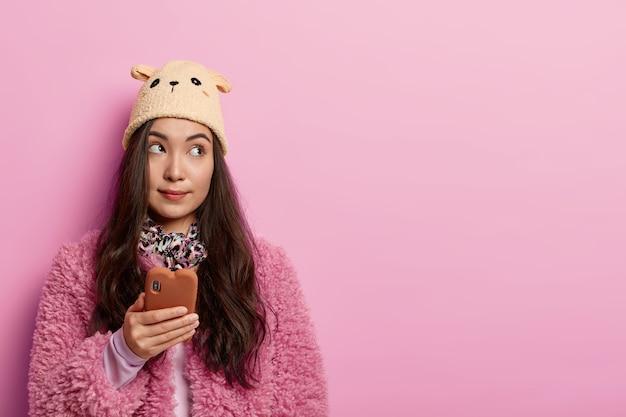 Poziomy widok zamyślonej kobiety o ciemnych włosach używa telefonu komórkowego do czatowania online, zastanawia się, który komentarz napisać pod postem