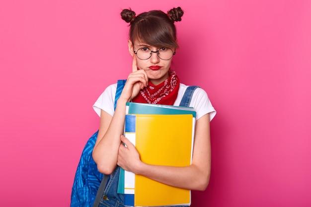 Poziomy widok zamyślonej uczennicy zaciska usta, trzyma palec wskazujący na brodzie, nosi okrągłe okulary, bandany na szyi, biały t-shirt, dżinsowy kombinezon, myśli o pracy domowej, stoi nad różową ścianą.