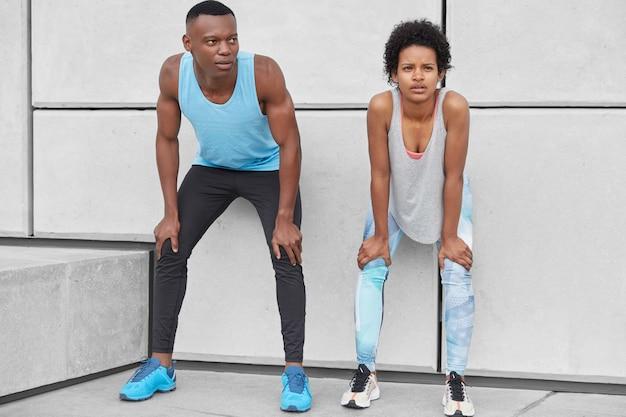 Poziomy widok zmęczonej kobiety i mężczyzny, pochyleni na kolanach, stań blisko białej ściany, złap oddech po intensywnym biegu, noś trampki, legginsy i koszulkę, miej kontemplacyjne miny