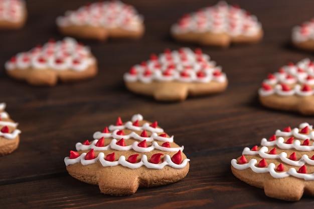 Poziomy wzór z ciasteczkami w kształcie choinki na ciemnym tle drewnianych