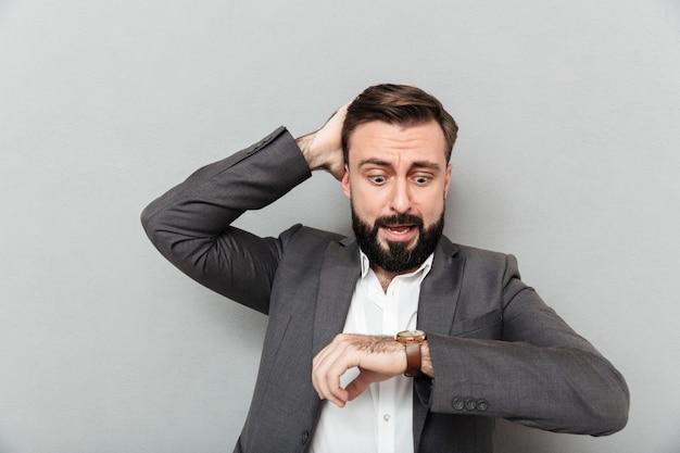 Poziomy zdumiony mężczyzna patrząc na zegarek, dotykając jego głowy spóźnia się pozować na szarym tle