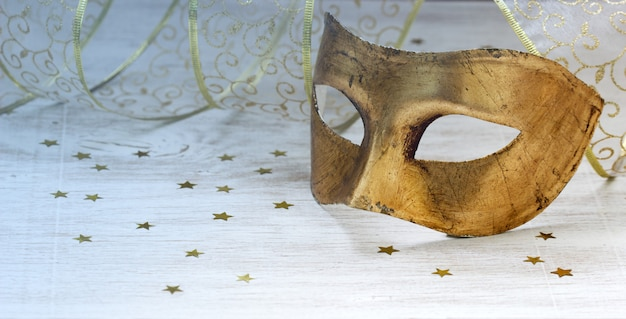 Pozłacane maski karnawałowe, wstążki i złote gwiazdki na jasnym tle.