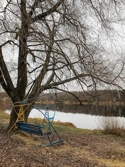 Późną jesienią krajobraz ze starymi huśtawkami na brzegu jeziora