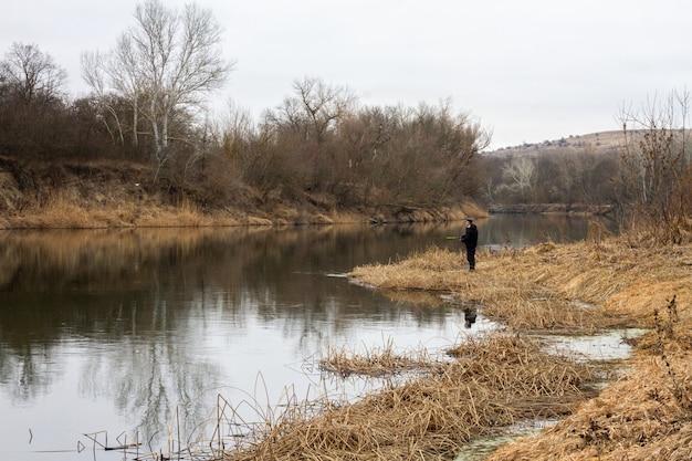 Późną jesienią mężczyzna łowi na rzece. piesze wędrówki na wolności