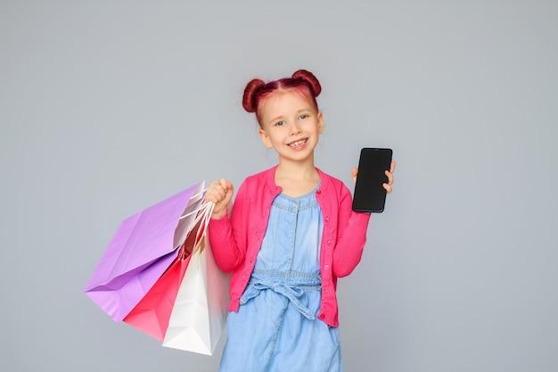 Poznaj rabaty. szczęśliwa mała dziewczynka uśmiecha się z papierowymi torbami na zakupy.