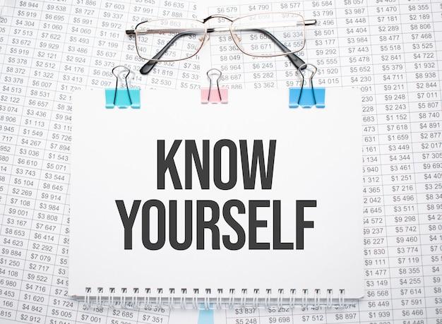 Poznaj siebie tekst napisany na papierze długopisem i okularami