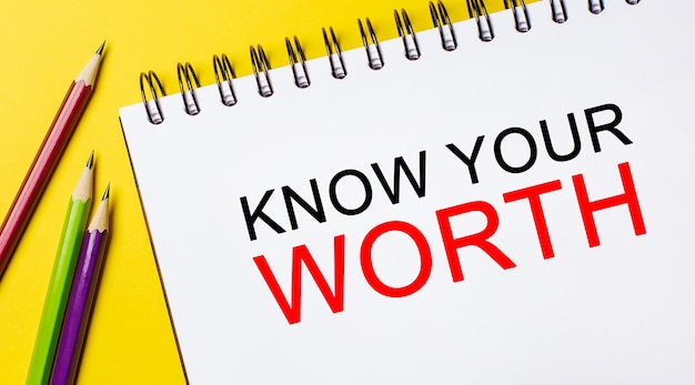 Poznaj swój wartość na białym notatniku z ołówkami na żółtym polu