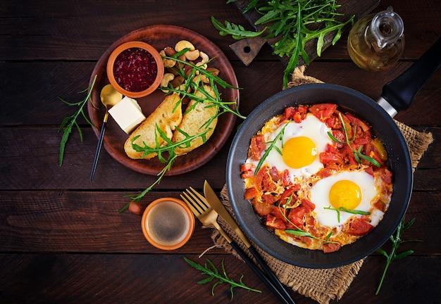 Późne śniadanie - jajka sadzone z warzywami. shakshuka. kuchnia arabska. koszerne jedzenie. widok z góry