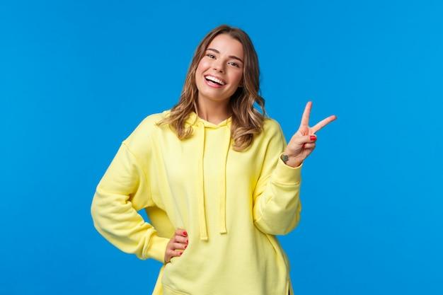 Pozostając jasny sie. beztroska szczęśliwa młoda głupia blond dziewczyna w żółtej bluzie z kapturem wysyłająca pozytywne wibracje, pokazująca znak pokoju kawaii i uśmiechnięta z białymi zębami, stojąca niebieska ściana