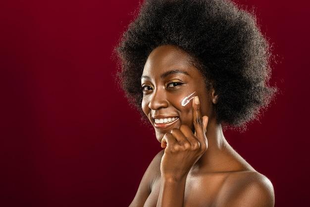 Pozostając pięknym. zachwycona sympatyczna kobieta, dbająca o swój wygląd przy użyciu kosmetyków