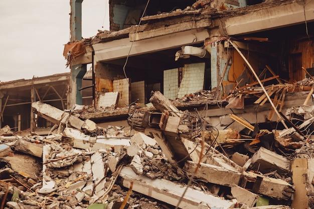 Pozostałości zniszczonego budynku przemysłowego z wewnętrzną komunikacją. rozbiórka budynku na terenie zakładu. tło z zniszczonymi fragmentami cegieł i gruzu budowlanego. skopiuj miejsce