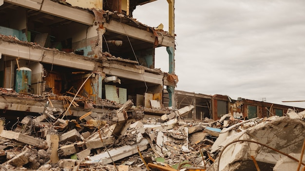 Pozostałości zniszczonego budynku przemysłowego z wewnętrzną komunikacją. rozbiórka budynku na terenie zakładu. tło ze zniszczonym budynkiem oraz fragmentami cegieł i gruzu budowlanego