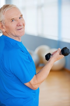 Pozostań aktywnym i zdrowym. widok z tyłu szczęśliwego starszego mężczyzny ćwiczącego z hantlami i patrzącego przez ramię, stojąc w klubie fitness