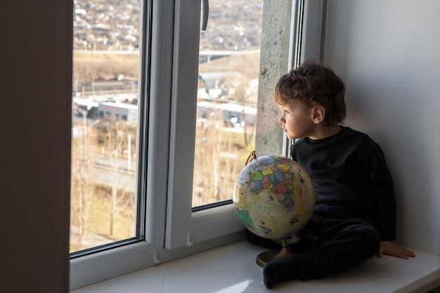 Pozostań pozytywnie w domu. dziecko siedzi na parapecie i bawi się kulą ziemską