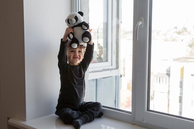 Pozostań pozytywnie w domu. wesoły i wesoły dziecko siedzi na parapecie i bawi się misiem panda