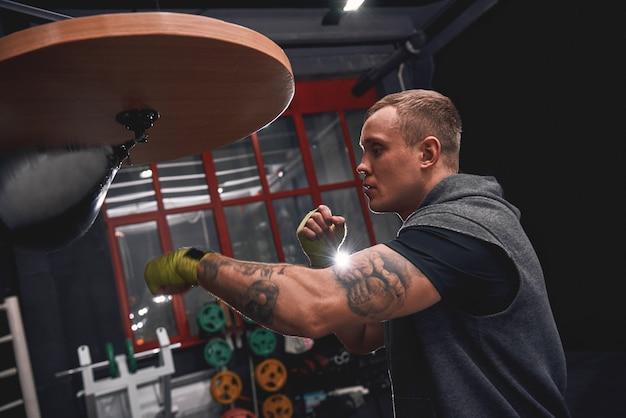 Pozostań silny, aby wygrać widok z boku profesjonalnego młodego boksera z uderzającymi bandażami zielonych rąk