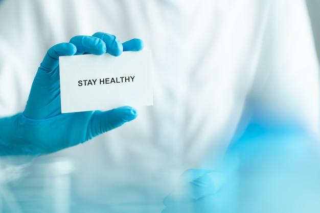 Pozostań w domu i zdrowo, aby zapobiec kampanii rozprzestrzeniania się covid-19, tekst na papierze z lekarzem w niebieskich rękawiczkach