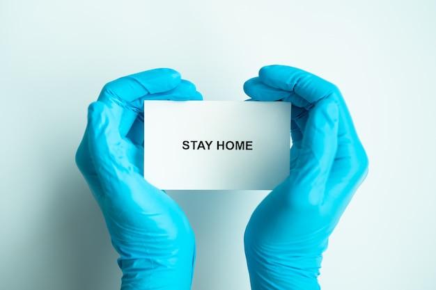 Pozostań w domu i zdrowo, aby zapobiec kampanii rozprzestrzeniania się covid-19, tekst na papierze z rękami w kształcie serca lekarza w niebieskich rękawiczkach