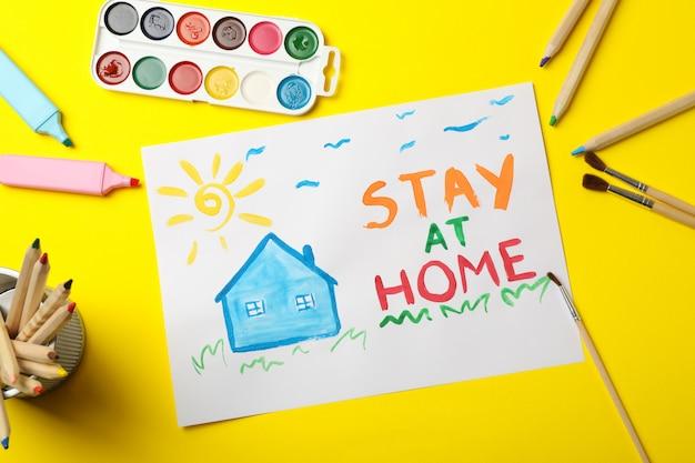 Pozostań w domu koncepcja na żółtej powierzchni. miejsce do rysowania dla dzieci