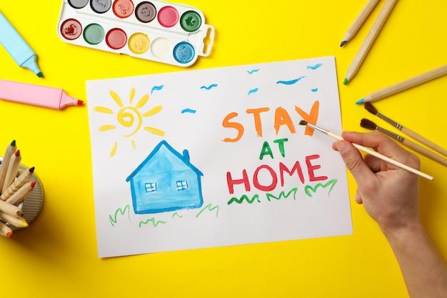 Pozostań w domu koncepcja na żółtej powierzchni. pędzel do trzymania osoby